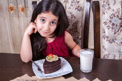 Young small beautiful middle eastern child girl with chocolate cake with pineapple, strawberry, and milk with red dress and dark e Stock Image