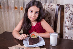 Young small beautiful middle eastern child girl with chocolate cake with pineapple, strawberry, and milk with red dress and dark e Stock Photo