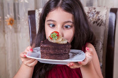 Young small beautiful middle eastern child girl with chocolate cake with pineapple, strawberry, and milk with red dress and dark e Stock Images