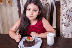 Young small beautiful middle eastern child girl with chocolate cake with pineapple, strawberry, and milk with red dress and dark e Royalty Free Stock Photography