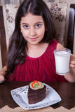 Young small beautiful middle eastern child girl with chocolate cake with pineapple, strawberry, and milk with red dress and dark e Stock Photography
