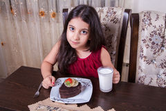 Young small beautiful middle eastern child girl with chocolate cake with pineapple, strawberry, and milk with red dress and dark e Royalty Free Stock Image