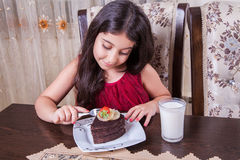 Young small beautiful middle eastern child girl with chocolate cake with pineapple, strawberry, and milk with red dress and dark e. Small beautiful middle Stock Images