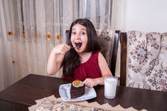 Young small beautiful middle eastern child girl with chocolate cake with pineapple, strawberry, and milk with red dress and dark e Royalty Free Stock Photos