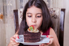 Young small beautiful middle eastern child girl with chocolate cake with pineapple, strawberry, and milk with red dress and dark e Stock Photos