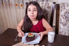 Free Young Small Beautiful Middle Eastern Child Girl With Chocolate Cake With Pineapple, Strawberry, And Milk With Red Dress And Dark Royalty Free Stock Images - 57170989