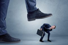 Trampled small businessman in suit. Young small businessman is trampled by a big foot in an empty space Stock Photo