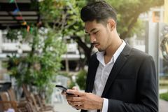 Smart young businessman playing smartphone stock image