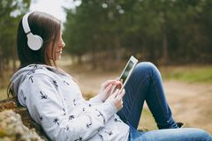 Young smart beautiful woman in casual clothes with headphones sitting on stone using tablet pc computer in city park or royalty free stock photo
