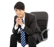 Young smart businessman sitting in a chair. Over white background Stock Photo