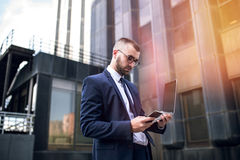 Young smart businessman using a computer and a phone Royalty Free Stock Images