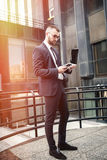 Young smart businessman using a computer and a phone Royalty Free Stock Photography