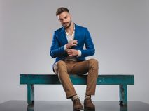 Seated smart casual man in blue suit fixes his cuffs. Young smart casual man in blue suit sits on wooden bench and fixes his cuffs, full length picture stock photo