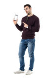 Young smart casual man showing finger advertising blank mobile phone display. Stock Images