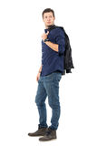 Young smart casual man walking while carrying jacket over shoulder looks back. stock image