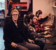 A young smart gamer wearing a sweater and glasses sitting on a gamer chair and looking at a camera in a gaming club or. A smart gamer wearing a sweater and stock photo
