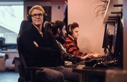 A young smart gamer wearing a sweater and glasses sitting on a gamer chair and looking at a camera in a gaming club or. A smart gamer wearing a sweater and royalty free stock images