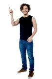 Young smart guy pointing upwards Royalty Free Stock Image