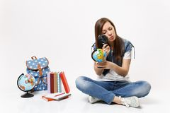 Young smart interested woman student looking on globe with magnifying glass learning sitting near backpack, school books stock photos