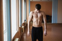 Young smart man trains in the hall for training. Tight body Stock Image