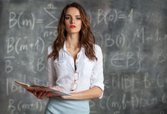 Young smart pretty woman with textbook near blackboard. Young smart woman holding book in her hands  near blackboard with math calculations Stock Image
