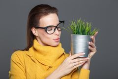 Young smart woman in eyeglasses holding indoor plant in metal po. T, smile Stock Photos