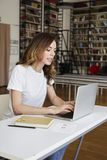 Young smart woman long hair analyst working at co-working office on laptop, bookshelf in library.  royalty free stock photo