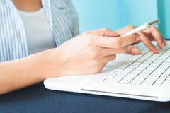 Young smart woman using mobile device and laptop computer, Techn Royalty Free Stock Image