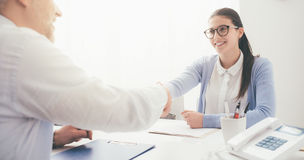Successful job interview. Young smart women having a successful job interview, the examiner is shaking her hand royalty free stock photo