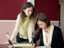 Two young smartly dressed women filling out forms at a vintage office desk in front of a laptop stock image