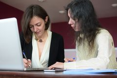 Young smartly dressed lady helps another young lady to work with documents, fill forms and sign. They sit together in a vintage style office at a vintage desk royalty free stock image