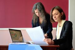 Young smartly dressed lady helps another young lady to work with documents, fill forms and sign stock photos