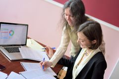 Young smartly dressed lady helps another young lady to work with documents, fill forms and sign. They sit together in a vintage royalty free stock photo