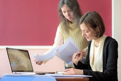 Young smartly dressed lady helps another young lady to work with documents, fill forms and sign. They sit together in a vintage style office at a vintage desk stock photos