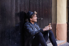 Young smartphone man sitting street Stock Image