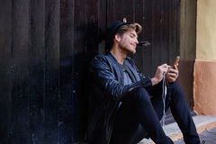 Young smartphone man sitting street Royalty Free Stock Images