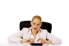 Young smile business woman sitting behind the desk and using calculator Stock Photography