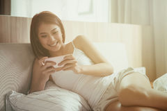 Young smile woman playing smart phone lying on the bed at home. royalty free stock image