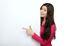 Young smile woman pointing at a blank board. Young smile woman standing pointing her finger at a blank board Royalty Free Stock Image