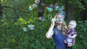 Young mother with smiled baby girl blow bubble in park. 4K. Young smiled mother with baby girl blow soap bubble at sunny day in green park. Game and freetime in stock video