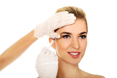 Young smiled woman is having facial botox injection. stock photography