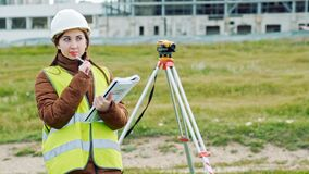 Young smileing woman surveyor in green work clothes and helmet adjusts the equipment, produces calculations and writes