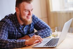 Young smiles man working on laptop at home royalty free stock images