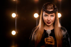 Young smiley beautiful girl on the stage in karaoke. Young smiley beautiful long hair girl in black dress with microphone singing song on the stage in karaoke Stock Photo
