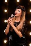 Young smiley beautiful girl on the stage in karaoke. Young smiley beautiful long hair girl in black dress with microphone singing song on the stage in karaoke Stock Image