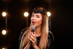 Young smiley beautiful long hair girl in karaoke. Young smiley beautiful long hair girl in black dress with microphone singing song on the stage in karaoke Royalty Free Stock Photos