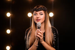 Young smiley beautiful long hair girl in karaoke. Young smiley beautiful long hair girl in black dress with microphone singing song on the stage in karaoke Stock Photos