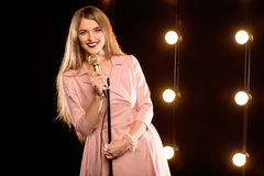 Young smiley beautiful long hair girl with microphone singing. Song on the stage in karaoke Stock Photo