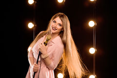 Young smiley beautiful long hair girl with microphone singing. Song on the stage in karaoke Stock Photography
