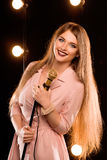 Young smiley beautiful long hair girl with microphone singing. Song on the stage in karaoke Stock Images